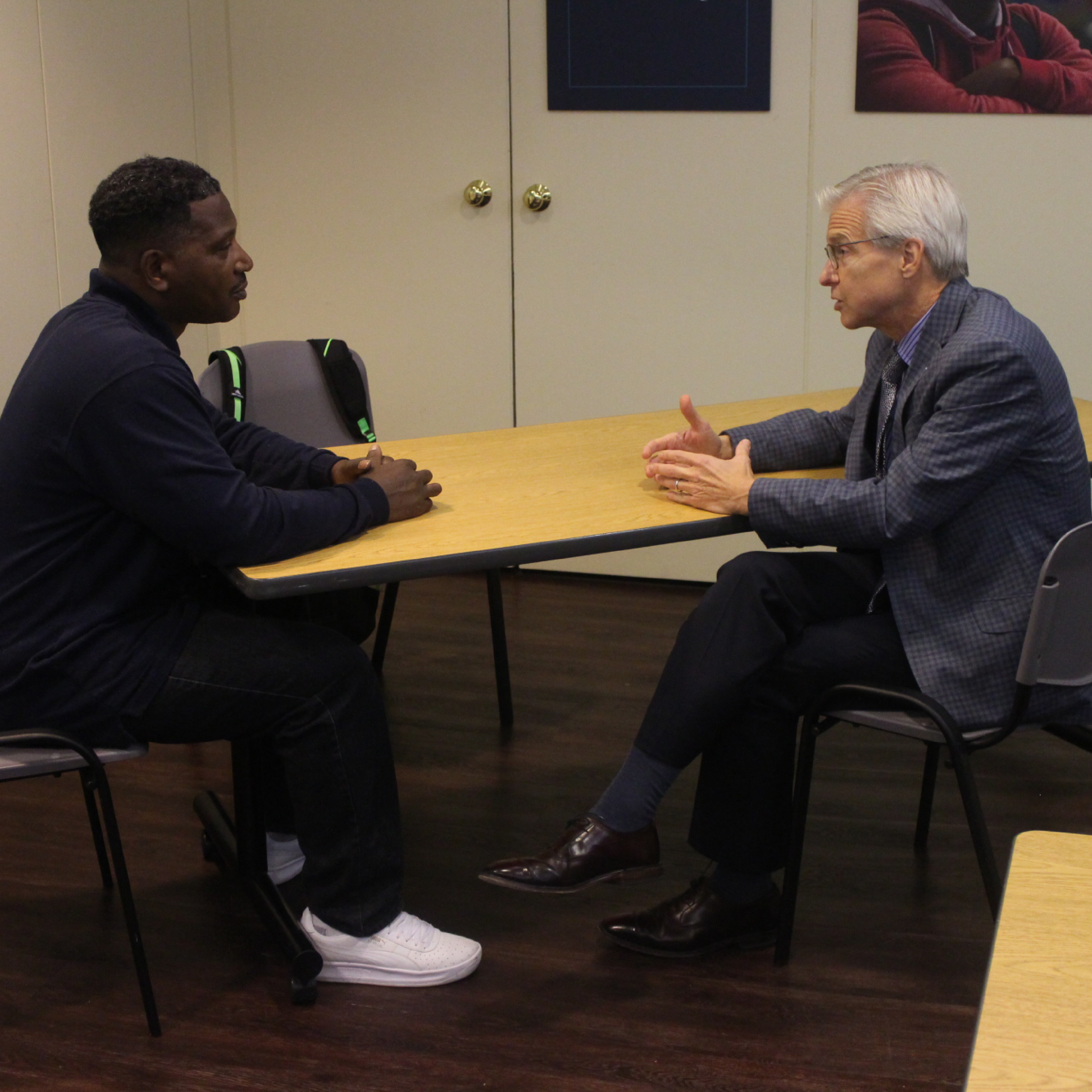An ECS volunteer and board member helps a workforce development participant hone his interview skills
